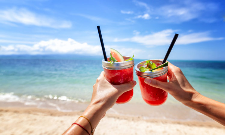 Two people are enjoying their holiday abroad with tropical drinks